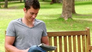 Man reading a newspaper before looking at the camera as he sits on a bench