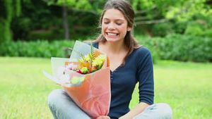 Cheerful young woman smelling flowers
