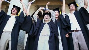 Happy graduated students raising their arms
