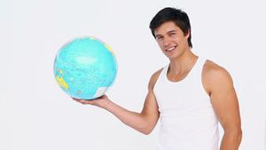 Man spins a globe in his hand