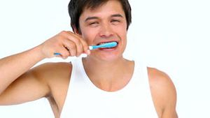 Man brushing and looking his teeth