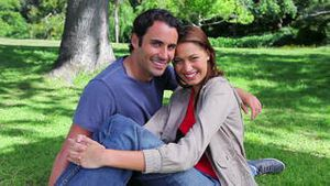 Smiling couple sitting on the grass