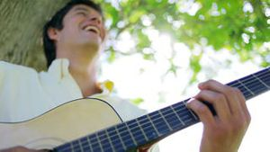Cheerful man playing the guitar