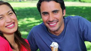 Smiling couple eating cones