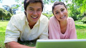 Smiling couple using their laptop