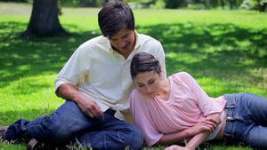 Happy couple reading while sitting on the grass