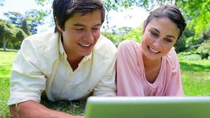 Smiling couple lying on the grass while watching a laptop