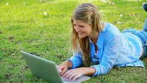 Woman using computer while lying on front