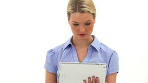Cheerful blonde woman using a tablet computer