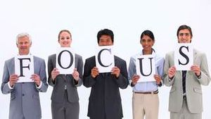 Business people holding supports with the word FOCUS