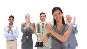 Woman holding a trophy with coworkers applauding