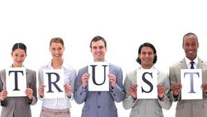 Business people holding boards with the word TRUST