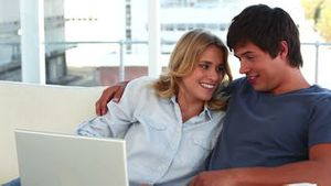 Lovely couple looking at a laptop