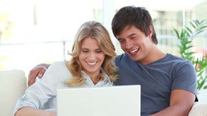 Happy couple talking in front of a laptop
