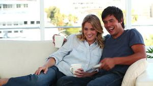 Smiling couple looking at the television
