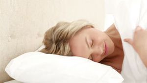 Smiling woman turning off her alarm