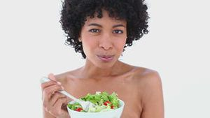 Black haired woman eating salad