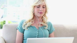 Blonde haired woman listening to music on a laptop