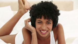 Young black haired woman listening to music