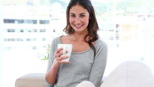 A woman relaxes with a cup of coffee