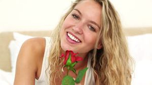 Blonde haired woman smelling a red rose