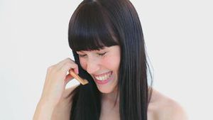 Happy woman combing her hair while laughing