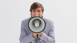 Serious businessman talking into a megaphone