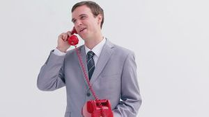 Happy businessman using a red phone