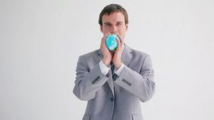 Happy executive playing with a globe ball