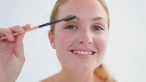 Smiling woman attentively brushing her eyebrows