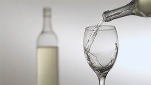 White wine poured in super slow motion in a glass