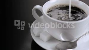 Milk flowing in super slow motion in coffee