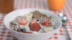 Strawberry falling in super slow motion in cereal bowl