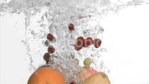 Fruits in super slow motion falling in the water