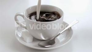 Milk dripping in super slow motion in a coffee cup