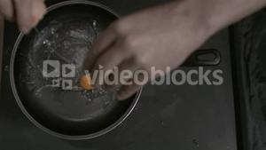 Egg in super slow motion being placed in a pan