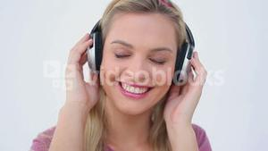 Smiling blonde woman listening to music