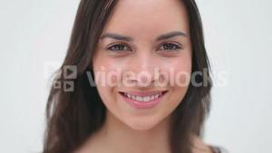 Happy brunette turns her head and looks at the camera
