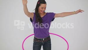 Smiling woman playing with a hula hoop