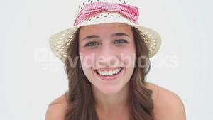 Happy woman wearing a hat while hiding her face