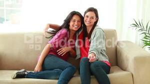 Happy women running then sitting on a couch