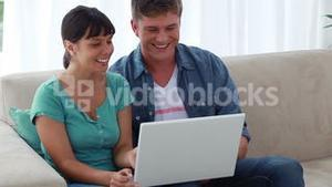 Happy couple looking at their personal computer