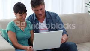 Happy couple looking at a laptop together
