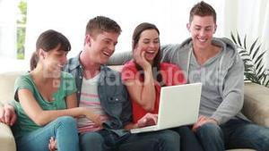 Smiling friends laughing in front of a laptop