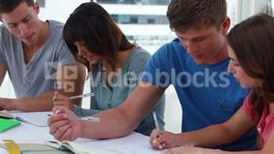 Serious students helping each other while working