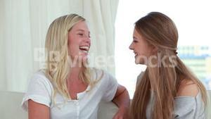 Smiling friends chatting together while sitting on a sofa