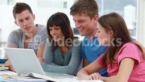 Smiling students using a laptop together