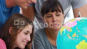 Smiling students pointing at countries on a globe