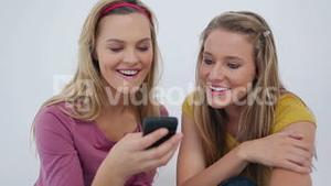 Laughing friends text messaging