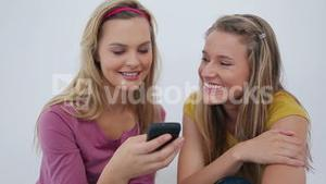 Female friends sending a text message together